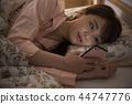 少婦在床上的看智能手機 44747776