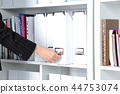 Business woman takes a folder that is on the shelf in the office. 44753074