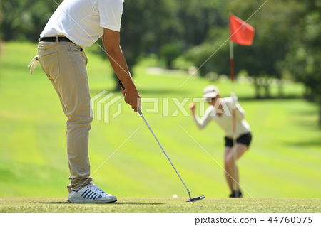Man and woman playing golf  44760075