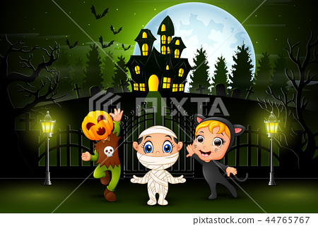 Happy halloween kids outdoors with haunted house b 44765767