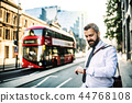 Hipster businessman standing on the street in London, checking the time. 44768108