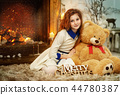 Little girl sitting in front of fireplace at Christmas 44780387