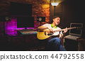 asian artist singing and playing guitar in studio 44792558
