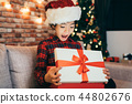 little girl surprised open christmas gift at home 44802676