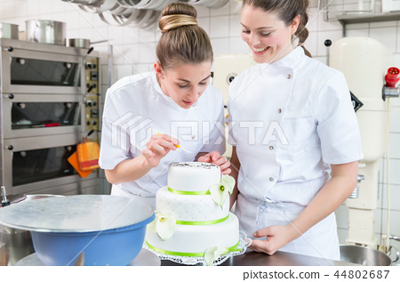 Two pastry bakers decorating large cake 44802687