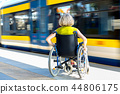 woman sitting on wheelchair on a platform 44806175