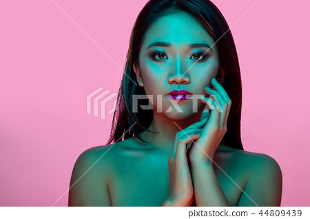 High Fashion model woman in colorful bright lights posing in studio 44809439