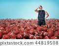 A thoughtful muscular man stands in a field of identical American football balls. 44819508