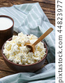 Cottage cheese with wooden spoon in it and milk  44823977