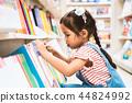 asian girl select book on bookshelf in bookstore 44824992
