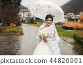 Happy beautiful bride in her weddind day walking in the park. use umbrella 44826961