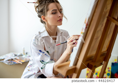 Closeup of beautiful woman painting on canvas in studio 44828417