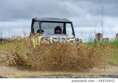 ATV brp is moving on a muddy puddle making splashes 44839842