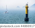 Yellow black lighthouse and sail boat in the sea 44860917