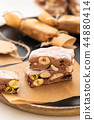 A variety of different nutty nougat in dark chocolate with roasted hazelnuts cut open to show the 44880414