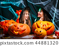 Happy Halloween. Mother and her daughter in witch costumes having fun at home. 44881320