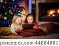 Two cute little sisters using a tablet pc by a fireplace on Christmas evening 44884861