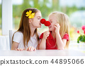 Happy little sisters wearing red clown noses having fun together on sunny summer day at home 44895066
