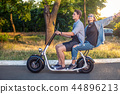Lovely young couple driving electric bike during summer 44896213