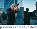 Bodyguard with security earpiece and gun in hands 44925628
