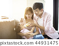 happy father and mother feeding baby from bottle 44931475