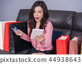 surprised woman using laptop computer for online shopping with c 44938643