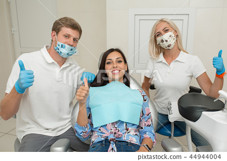 A dentist, his assistant and happy female patient 44944004