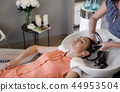 Grinning lady is enjoying water care in cozy salon 44953504