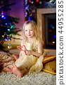 Christmas portrait of happy little girl by a fireplace in a cozy dark living room 44955285