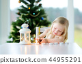 Beautiful little girl lighting a candle in white lantern 44955291