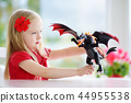 Cute little girl playing with toy dragon 44955538