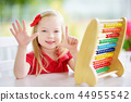 Cute little girl playing with abacus at home. Smart child learning to count. 44955542