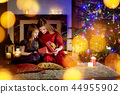 Mother and daughter unwrapping Christmas gifts 44955902