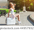 Girl traveler with a white suitcase 44957932