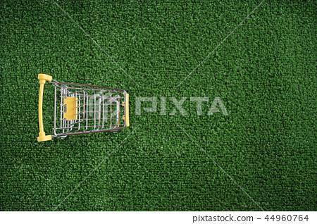 Yellow shopping cart on green artificial grass 44960764
