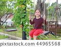 Happy child girl sitting on the swing in the park. 44965568
