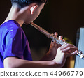 Back view of  a male musician student plays flute 44966779