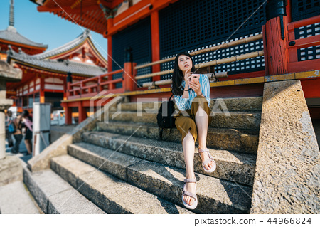 traveler sitting on stairs after visited temple 44966824