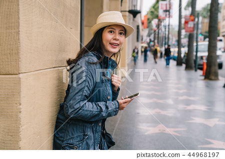an elegant woman relying on the wall 44968197