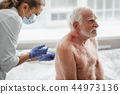 Shirtless old man receiving injection in back while sitting on hospital bed 44973136