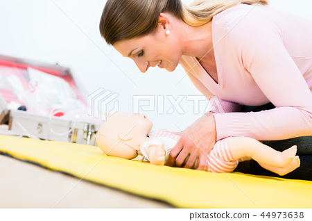 Woman in first aid course practicing revival of infant on baby d 44973638