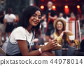 Charming girl enjoying meal during outdoor concert 44978014