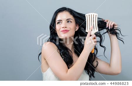 Beautiful young woman holding a hairbrush 44986823