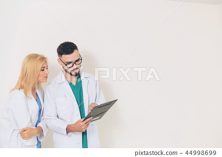 Doctors looking and discussing on documents paper. 44998699