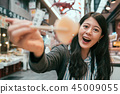 beautiful tourist showing sashimi by chopsticks 45009055