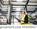 An industrial woman engineer with headset and clipboard in a factory, working. 45009607