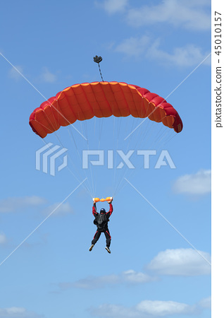 Parachutist floating to a square-shaped parachute. 45010157