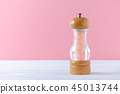 pink himalayan salt crystals in a glass wooden grinder on pink background 45013744