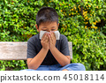 Asian boy blow his nose into with tissue in garden, Flu season, Hay fever. 45018114