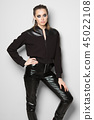 Woman in zipper sweater and faux leather pants 45022108